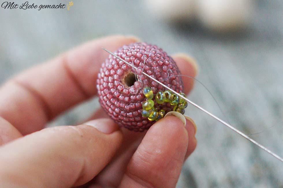 Faden durch Perle einfädeln