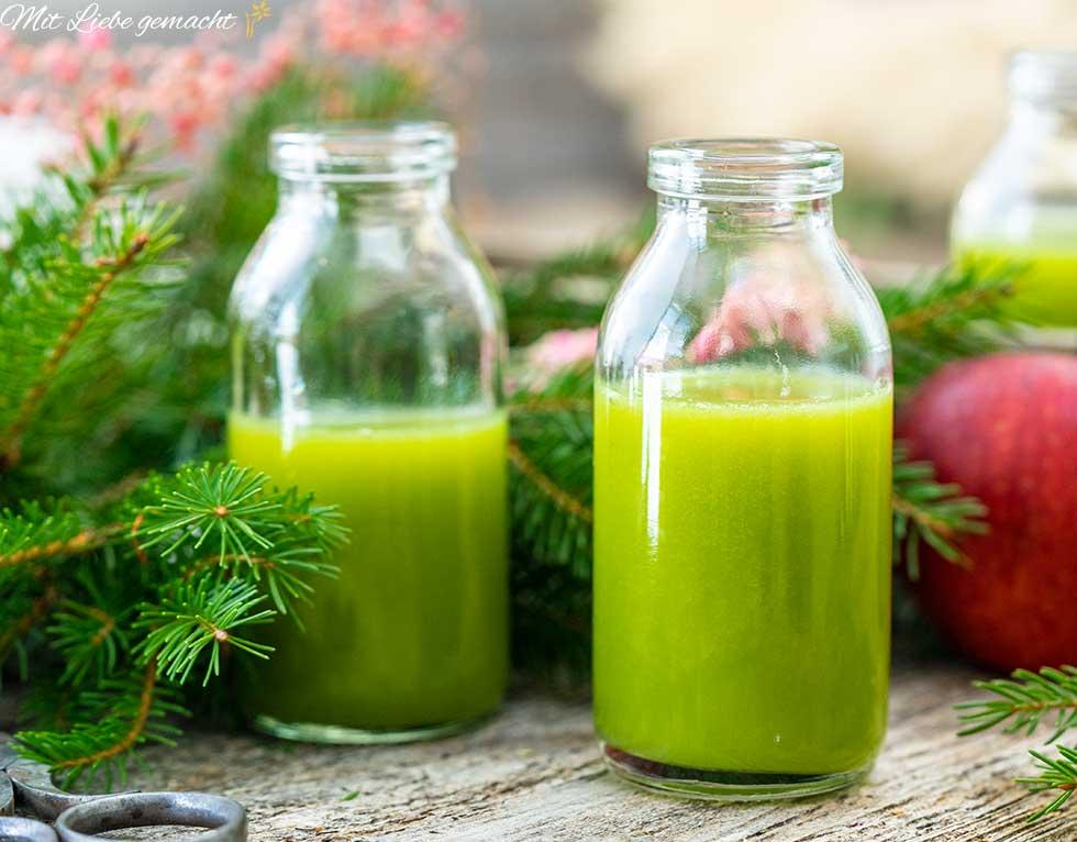 Fichtenzweig, Gläser mit grünem Smoothie, roter Apfel, Holztisch