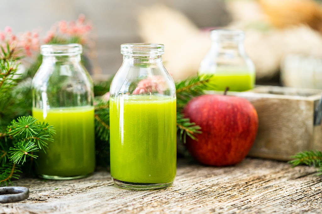 Grüner Smoothie in Glas, roter Apfel, grüne Zweige, Holztisch