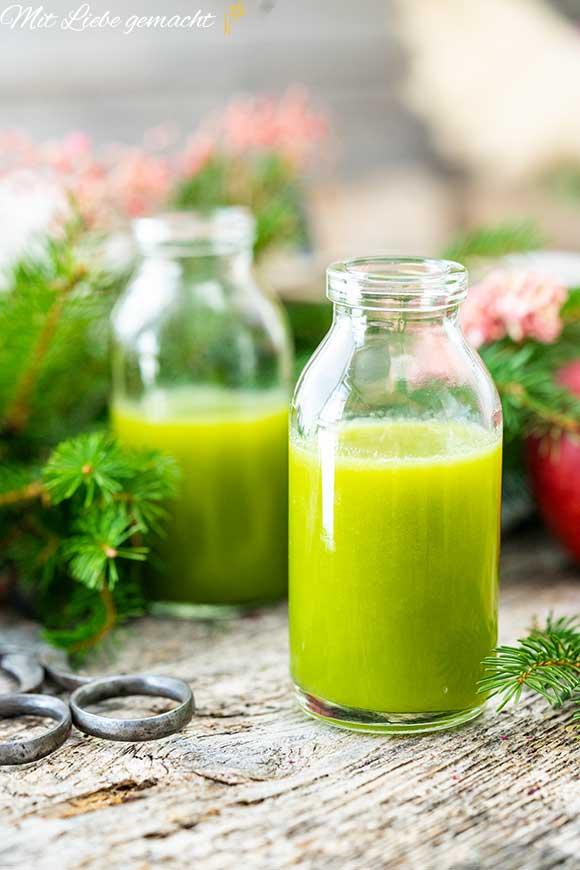Glas mit grünem Saft, Holztisch, grüne Zweige