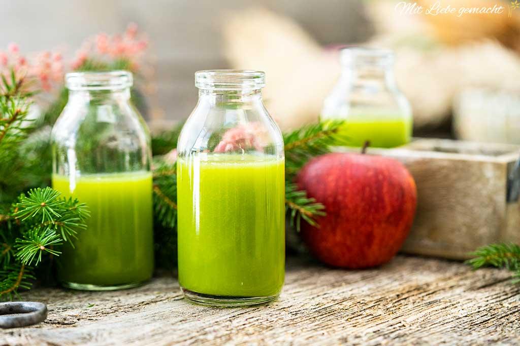 Gläser mit grünemSmoothie; Holztisch, Fichtenzweige, roter Apfel
